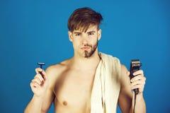 Jeune homme tenant le rasoir de sécurité et le rasoir électrique image stock