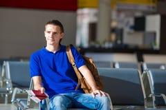 Jeune homme tenant les passeports et la carte d'embarquement à Photographie stock