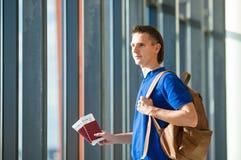 Jeune homme tenant les passeports et la carte d'embarquement à Photos stock