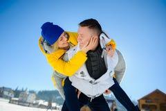 Jeune homme tenant son amie sur ses épaules Images stock