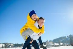 Jeune homme tenant son amie sur ses épaules Photographie stock libre de droits