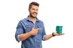 Jeune homme tenant un petits bac de recyclage et pointage Photographie stock libre de droits