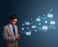 Jeune homme tenant un téléphone avec des flèches et des icônes de message Photo stock
