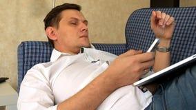 Jeune homme travaillant à distance le mensonge sur le sofa avec l'ordinateur portable et le téléphone banque de vidéos