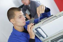Jeune homme travaillant au photocopieur avec le tournevis image libre de droits