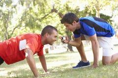 Jeune homme travaillant avec l'entraîneur personnel In Park images stock