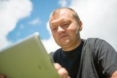 Jeune homme travaillant avec l'ipad image stock