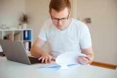 Jeune homme travaillant avec l'ordinateur portatif à la maison images libres de droits