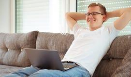 Jeune homme travaillant avec l'ordinateur portatif à la maison photos libres de droits