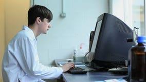 Jeune homme travaillant avec un ordinateur banque de vidéos