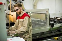 Jeune homme travaillant dans l'usine photos stock