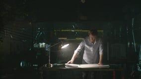 Jeune homme travaillant dans le bureau moderne la nuit L'architecte ouvre le dessin banque de vidéos