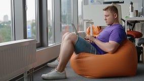 Jeune homme travaillant dans le bureau moderne se reposant sur le sac de sable clips vidéos
