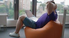 Jeune homme travaillant dans le bureau moderne se reposant sur le sac de sable banque de vidéos