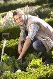 Jeune homme travaillant dans le jardin Images libres de droits