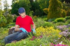 Jeune homme travaillant dans le jardin photo stock