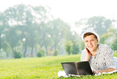 Jeune homme travaillant en parc avec un ordinateur portable image libre de droits