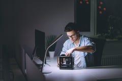 Jeune homme travaillant sur l'ordinateur la nuit dans le bureau foncé Photos stock