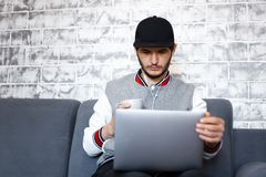 Jeune homme travaillant sur l'ordinateur portable, avec du café dans des mains sur le fond du mur de briques gris photo libre de droits