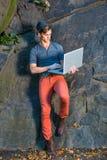 Jeune homme travaillant sur l'ordinateur portable dehors à côté des roches Images libres de droits