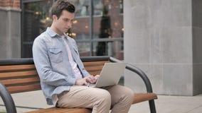 Jeune homme travaillant sur l'ordinateur portable, se reposant sur le banc banque de vidéos