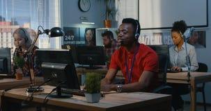 Jeune homme travaillant ? un centre d'assistance clips vidéos