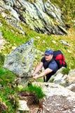 Jeune homme trimardant sur la traînée de montagne difficile avec le câble accrochant Photo libre de droits