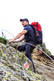 Jeune homme trimardant sur la traînée de montagne difficile avec le câble accrochant Photographie stock libre de droits