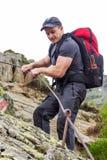 Jeune homme trimardant sur la traînée de montagne difficile avec le câble accrochant Images libres de droits