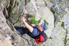Jeune homme trimardant sur la traînée de montagne difficile avec le câble accrochant Photos stock