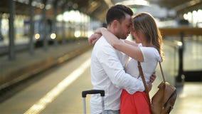 Jeune homme triste dans l'amour caressant et disant au revoir à son amie dans la gare ferroviaire avant le départ sur Sunny Day banque de vidéos