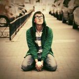 Jeune homme triste de hippie de mode s'asseyant sur le trottoir de ville Photos stock