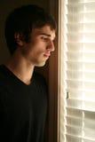 Jeune homme triste regardant à l'extérieur l'hublot photo stock