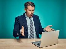 Jeune homme triste travaillant sur l'ordinateur portable au bureau images stock