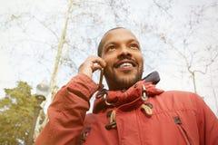 Jeune homme urbain de sourire heureux de hippie portant les vêtements informels et à l'aide du téléphone intelligent Hippie tenan Photos stock