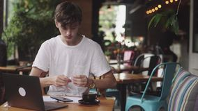 Jeune homme utilisant des écouteurs avec des fils à énumérer la musique en café, lieu de travail moderne se reposant en café Ordi clips vidéos