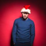 Jeune homme utilisant le chapeau rouge de Santa tenant des mains dans des poches Images stock