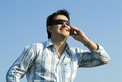Jeune homme utilisant un cellulaire Photographie stock libre de droits