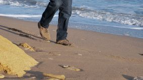 Jeune homme utilisant une paire de blues-jean et de bottes brunes marchant sur le rivage arénacé d'une belle plage banque de vidéos