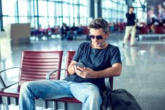 Jeune homme vérifiant le sien téléphone tout en attendant son vol dans le ciel image libre de droits