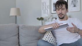 Jeune homme venant et s'asseyant sur le divan pour l'usage de l'ordinateur portable banque de vidéos