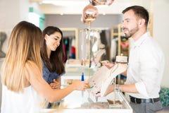 Jeune homme vendant des bijoux aux femmes Photo stock