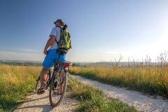 Jeune homme voyageant sur la bicyclette dans le lever de soleil de matin avec merveilleux photographie stock libre de droits