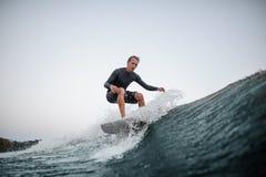 Jeune homme wakesurfing sur le conseil en bas de la vague bleue dans la perspective du ciel clair photo libre de droits