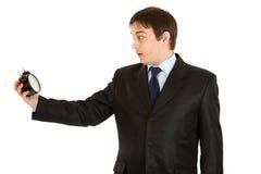 Jeune horloge d'alarme choquée de fixation d'homme d'affaires. Image stock