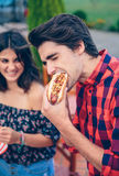 Jeune hot-dog et femme mangeurs d'hommes riant dedans Photos stock