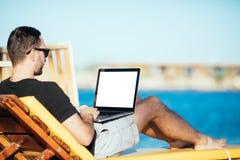 Jeune indépendant bel dans des lunettes de soleil fonctionnant avec l'ordinateur portable avec l'écran blanc pour l'espace de cop Photos libres de droits