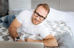 Jeune indépendant de sourire à l'aide de l'ordinateur portable et travaillant à la maison Photos stock