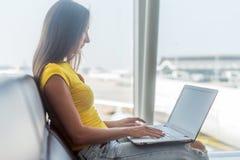 Jeune indépendant féminin à l'aide d'un ordinateur portable se reposant dans le terminal de départ d'aéroport attendant son vol Photographie stock