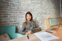 Jeune indépendant féminin avec du charme pensant à de nouvelles idées pendant le travail sur le pavé tactile Image libre de droits